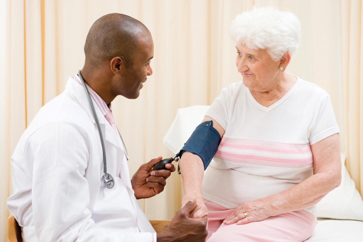 Un Cardiólogo Geriatra midiendo la presión arterial de un adulto mayor