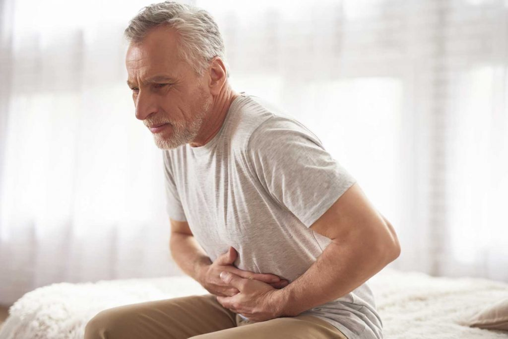 Se muestra adulto mayor con dolor en zona del estomago