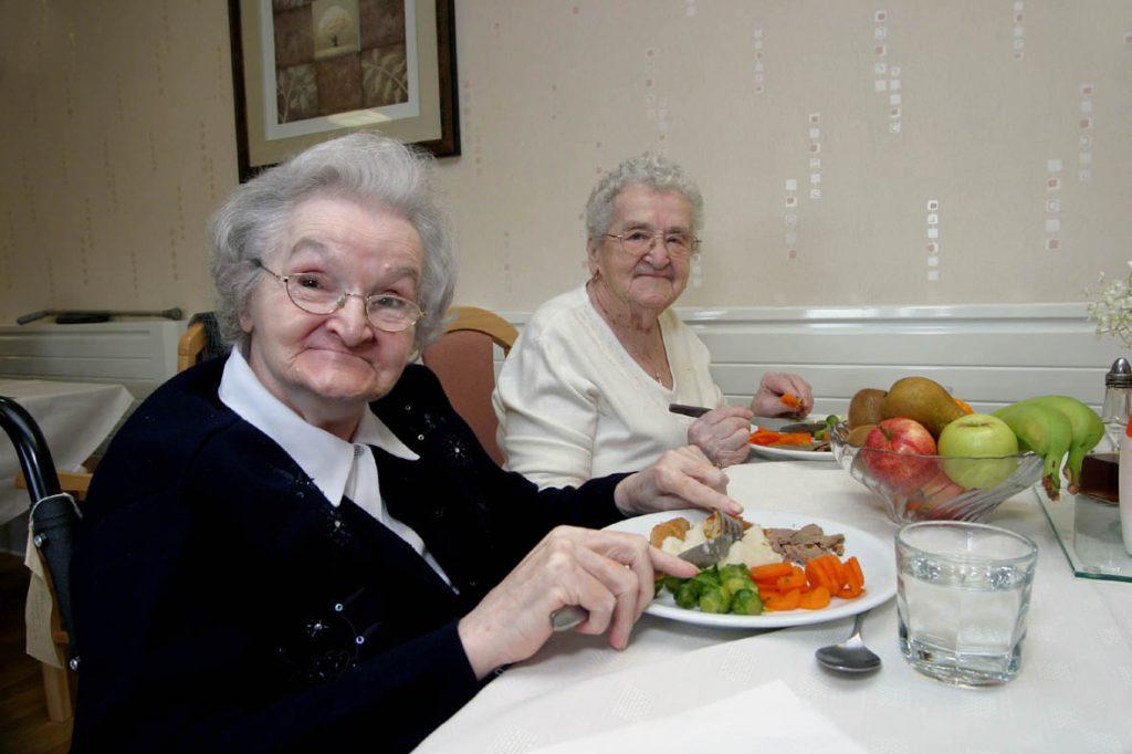 Se muestra a un par de mujeres adultas mayores comiendo ensalada