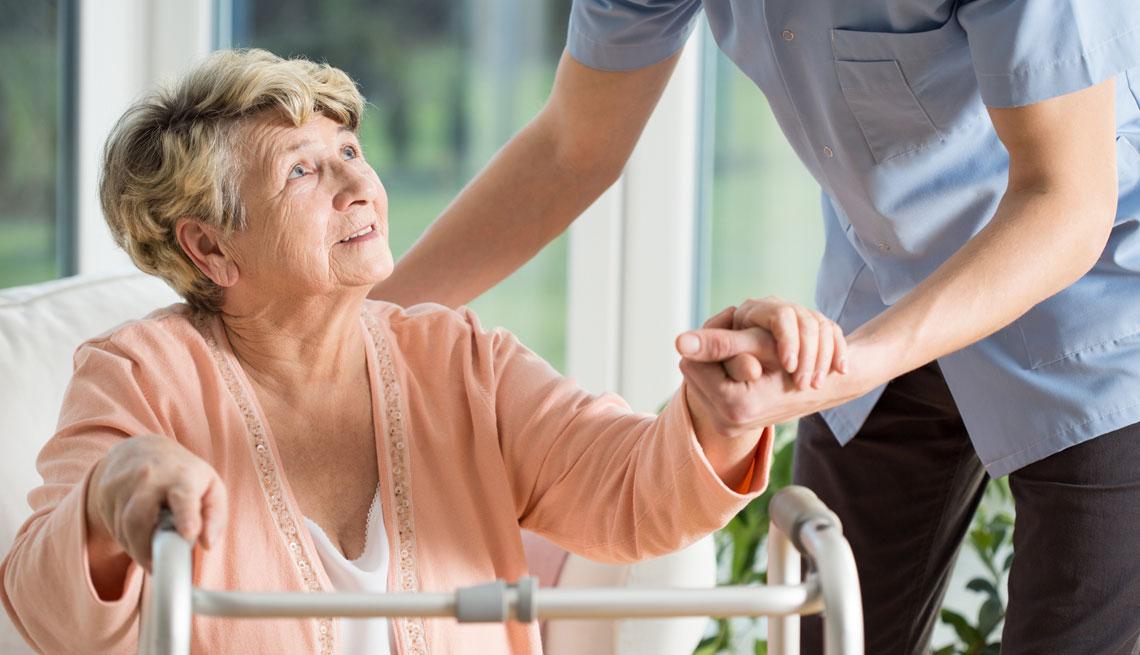 Adulto mayor siendo ayudado por un cuidador