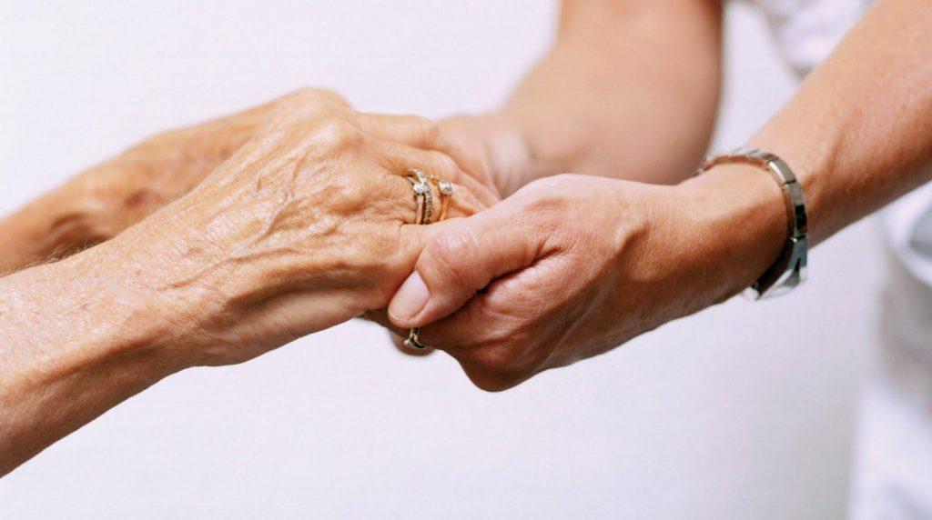 Persona sosteniendo las manos de un adulto mayor